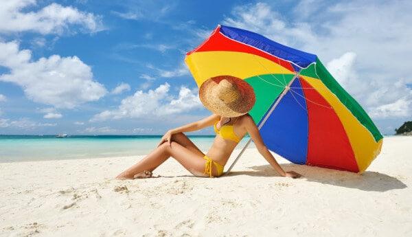 Screenshot van een vrouw in de zon onder een parasol.